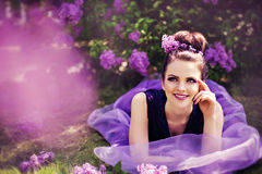 Smiling beautiful young girl lying in garden Royalty Free Stock Images