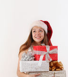 Smiling beautiful young girl in Santa hat with gifts dreaming ab Royalty Free Stock Photos