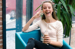 Smiling beautiful young girl talking on phone and drinking cocktail at the cafe. Portrait of beautiful smiling woman sitting on a. Comfortable chair in a cafe Stock Photography