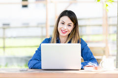 Smiling beautiful young girl using laptop computer stock images