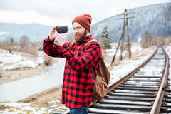 Smiling beautiful young man taking pictures with smartphone in mountains Royalty Free Stock Image