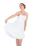 Smiling beautiful young model in white dress dancing Royalty Free Stock Image