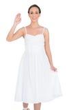 Smiling beautiful young model in white dress waving Stock Photo