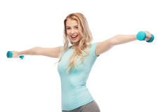 Smiling beautiful young sporty woman with dumbbell Royalty Free Stock Image