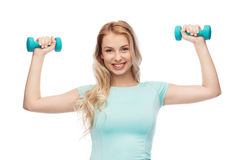 Smiling beautiful young sporty woman with dumbbell Stock Photo