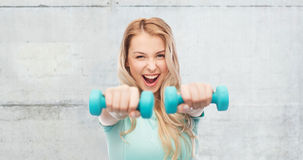 Smiling beautiful young sporty woman with dumbbell Stock Images