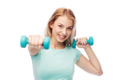 Smiling beautiful young sporty woman with dumbbell Royalty Free Stock Photography