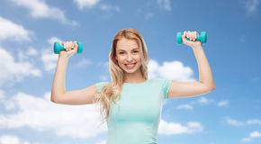 Smiling beautiful young sporty woman with dumbbell Stock Image