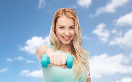 Smiling beautiful young sporty woman with dumbbell Royalty Free Stock Photo