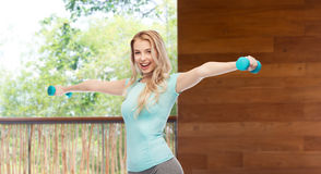 Smiling beautiful young sporty woman with dumbbell Stock Photography