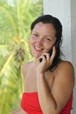 Smiling beautiful young woman with cellphone. Beautiful young woman in red dress smiling while talking on the phone outdoors. Palm trees and paradise in the Royalty Free Stock Image