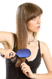 Young woman combing her long brown hair with hairbrush Stock Images