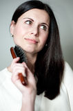 Woman combing her long hair Stock Images