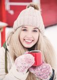 Smiling beautiful young woman drinks a hot cocoa outdoor. royalty free stock photography
