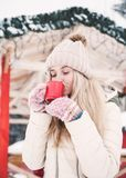 Smiling beautiful young woman drinks a hot cocoa outdoor. stock photography