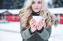 Beautiful smiling woman holds a cup of hot cocoa. royalty free stock image