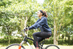 Smiling beautiful young woman exercising with bicycle, outdoor. Stock Images