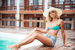 Smiling beautiful young woman in hat sitting near swiming pool. Full length of smiling beautiful young woman in hat sitting near swiming pool Royalty Free Stock Photography