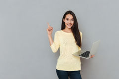 Smiling beautiful young woman holding laptop and pointing away. Over grey background royalty free stock images