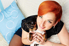 Smiling beautiful young woman holds her dog in her arms Stock Image