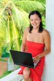 Smiling beautiful young woman with laptop. Smiling beautiful young woman in red dress with laptop on knee typing Stock Photo