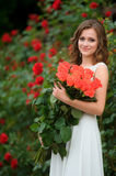 Smiling beautiful young woman with large bouquet of roses near b Royalty Free Stock Images