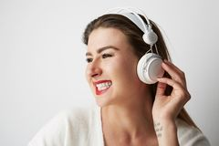 Smiling beautiful young woman listening to music on headphones over empty light background at studio. Horizontal. Stock Photo