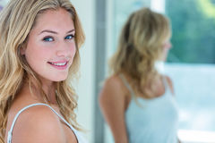 Smiling beautiful young woman looking at herself in the bathroom mirror Stock Image
