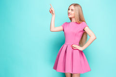 Smiling beautiful young woman in pink mini dress posing, presenting something. And looking away. Three quarter length studio shot on blue background Stock Photos