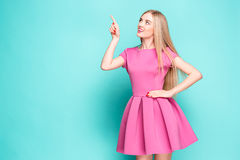 Smiling beautiful young woman in pink mini dress posing, presenting something. And looking away. Three quarter length studio shot on blue background Stock Photo