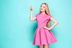 Smiling beautiful young woman in pink mini dress posing, presenting something. And looking away. Three quarter length studio shot on blue background Royalty Free Stock Images