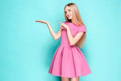 Smiling beautiful young woman in pink mini dress posing, presenting something. And looking at camera. Three quarter length studio shot on blue background Stock Photography