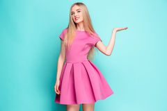 Smiling beautiful young woman in pink mini dress posing, presenting something. And looking at camera. Three quarter length studio shot on blue background Royalty Free Stock Photography