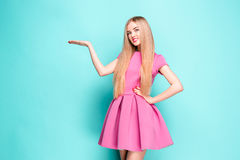 Smiling beautiful young woman in pink mini dress posing, presenting something. And looking at camera. Three quarter length studio shot on blue background Royalty Free Stock Image