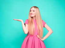 Smiling beautiful young woman in pink mini dress posing, presenting something. And looking at camera. Three quarter length studio shot on blue background Stock Images