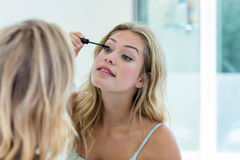 Smiling beautiful young woman putting on mascara in the bathroom mirror Royalty Free Stock Photos