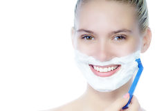 Smiling beautiful young woman shaving face Stock Images