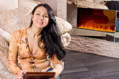 Smiling beautiful woman in front of a fire Royalty Free Stock Images