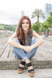 Smiling beautiful young woman sitting in the street. royalty free stock images