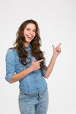Smiling beautiful young woman standing and pointing to the side Royalty Free Stock Photography