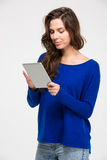 Smiling beautiful young woman standing and using tablet Royalty Free Stock Photos