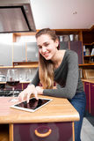 Smiling beautiful young woman touching a digital screen with wine. Smiling beautiful young woman touching a digital screen or tablet to read her online Stock Photos