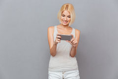 Smiling beautiful young woman using cell phone Royalty Free Stock Photo