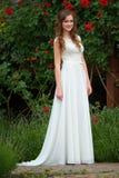 Smiling beautiful young woman wearing white dress posing near bl Stock Photo
