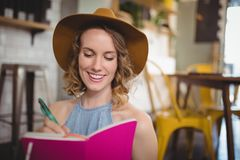 Smiling beautiful young woman writing in pink dairy. At coffee shop Royalty Free Stock Photography