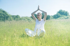 Smiling beautiful young yoga woman praying for toned spiritual mindfulness. Smiling beautiful young yoga woman praying with hands above her head in green meadow Royalty Free Stock Image