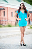 Smiling beauty in blue dress. On city streets Royalty Free Stock Photo