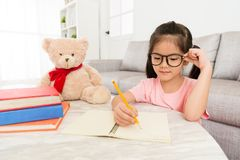 Smiling beauty female kid student studying at home. With teddy bear and writing school homework preparing back to school Royalty Free Stock Images