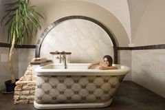 Smiling beauty girl in a bathtub Stock Images
