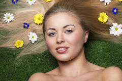 Smiling beauty girl with flowers. Close-up beauty portrait of blonde smiling female with perfect skin and natural make-up posing lying on green grass with some Royalty Free Stock Photos